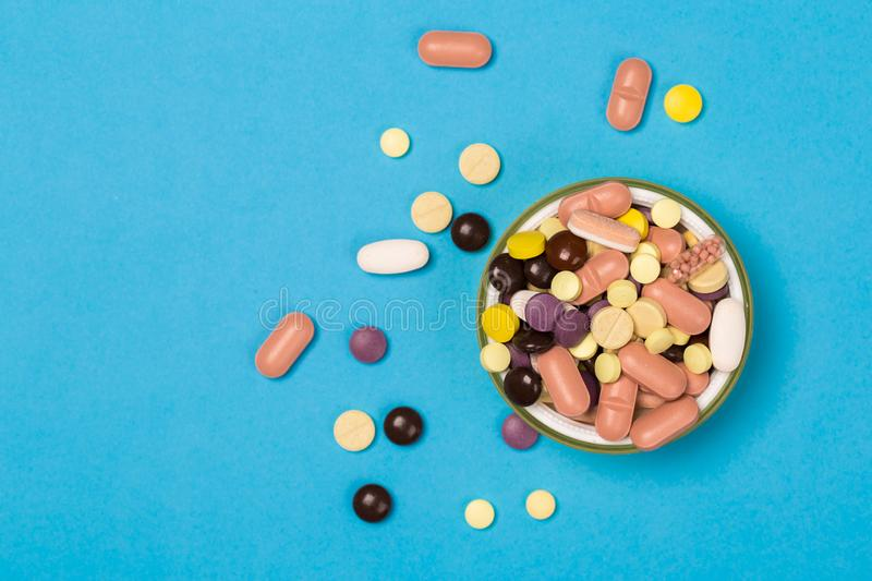 Assorted pharmaceutical medicine pills, tablets and capsules on  bowl on blue background. Assorted pharmaceutical medicine pills, tablets and capsules on  bowl royalty free stock photo