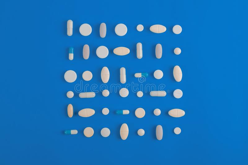 Assorted pharmaceutical white medicine pills, tablets. Assorted pharmaceutical medicine pills, tablets and capsules over blue background royalty free stock photos