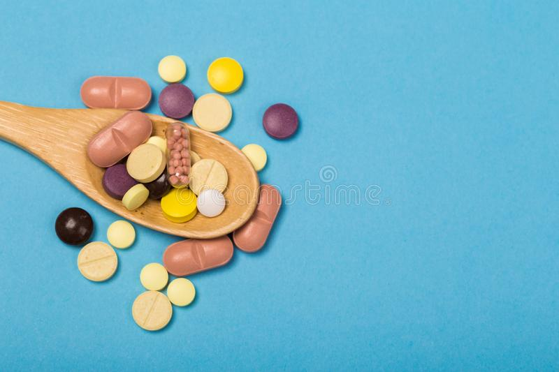 Assorted pharmaceutical medicine pills, tablets and capsules on wooden spoon. blue background. Assorted pharmaceutical medicine pills, tablets and capsules on stock photography