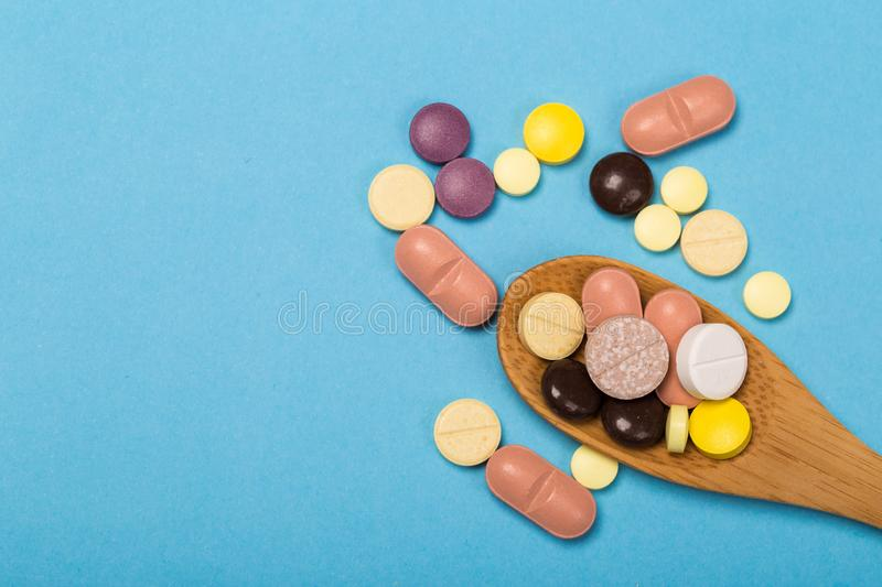 Assorted pharmaceutical medicine pills, tablets and capsules on wooden spoon. blue background. Assorted pharmaceutical medicine pills, tablets and capsules on royalty free stock images