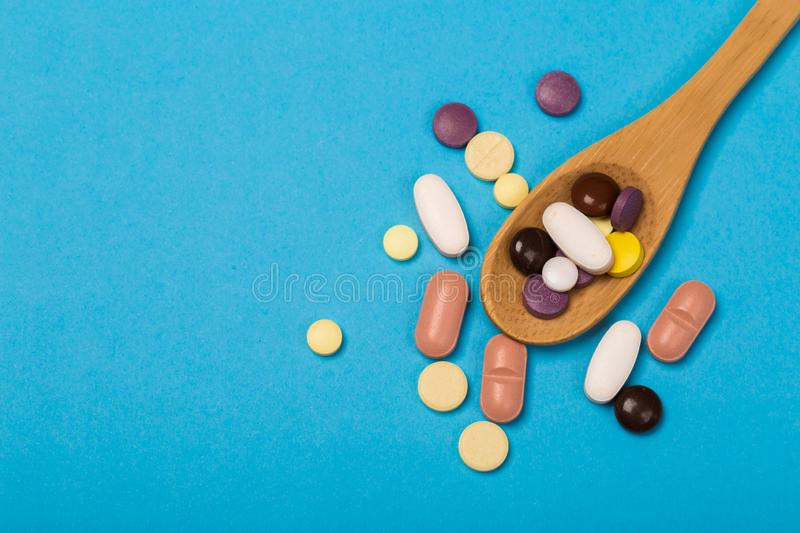 Assorted pharmaceutical medicine pills, tablets and capsules on wooden spoon. blue background. Assorted pharmaceutical medicine pills, tablets and capsules on stock images