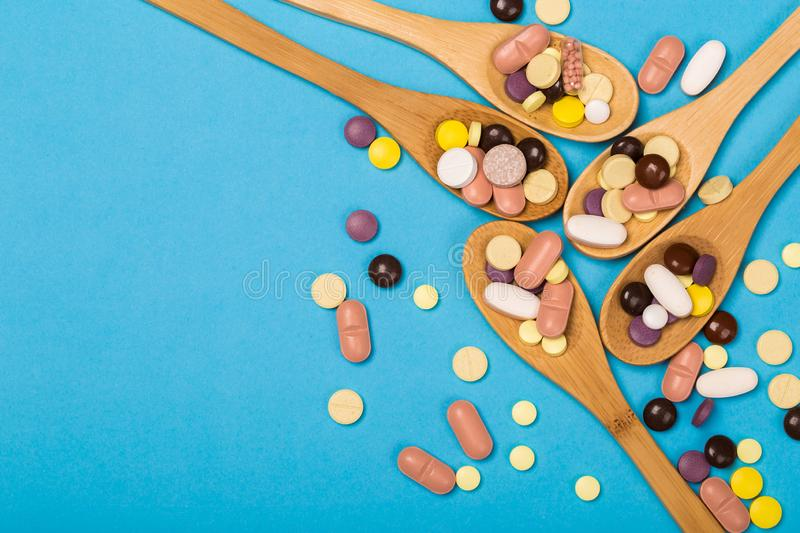 Assorted pharmaceutical medicine pills, tablets and capsules on wooden spoon. blue background. Assorted pharmaceutical medicine pills, tablets and capsules on royalty free stock photos