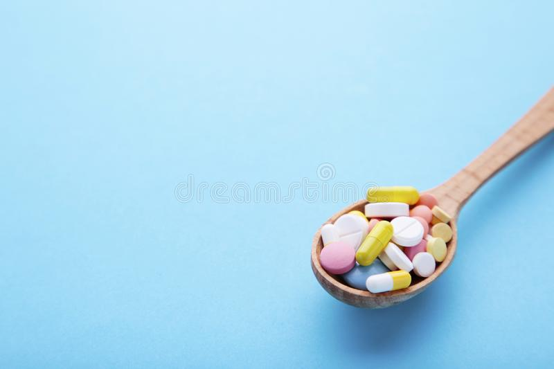 Assorted pharmaceutical medicine pills, tablets and capsules on wooden spoon on blue background stock photo