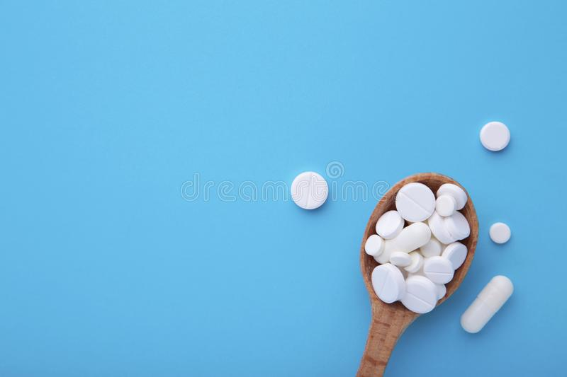 Assorted pharmaceutical medicine pills, tablets and capsules on wooden spoon on blue background. Assorted pharmaceutical medicine pills, tablets and capsules on royalty free stock photography