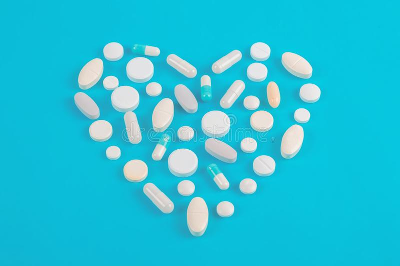 Assorted pharmaceutical medicine white pills, tablets and capsules. Over blue background royalty free stock photo