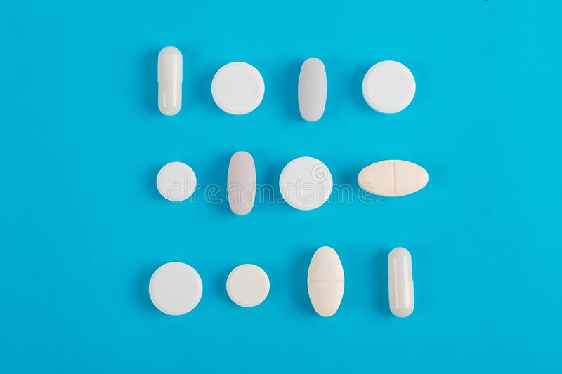 Assorted pharmaceutical white medicine pills, tablets. Assorted pharmaceutical medicine pills, tablets and capsules over blue background stock images