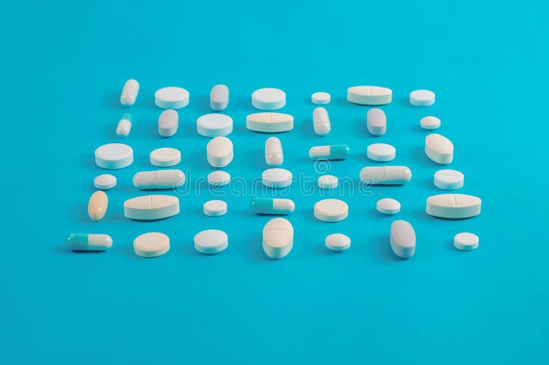 Assorted pharmaceutical white medicine pills, tablets. Assorted pharmaceutical medicine pills, tablets and capsules over blue background royalty free stock photography