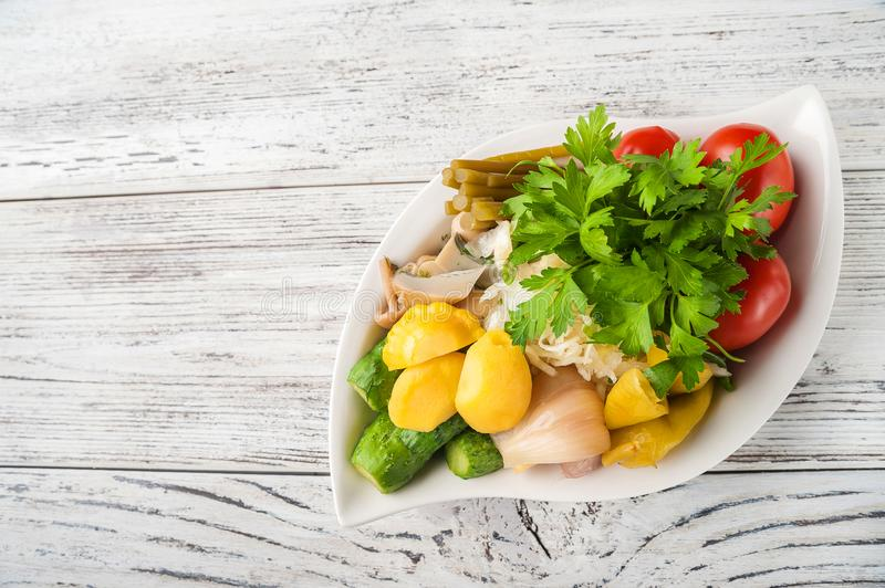 Assorted pickled vegetables in a white plate close-up. Marinated cucumbers, tomatoes, garlic, ramson, zucchini in a plate copy spa. Ce royalty free stock image