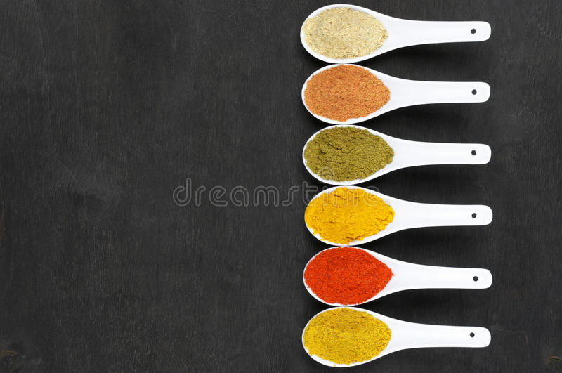 Assorted powder spices. In white spoons on black wood. Top view point stock photos