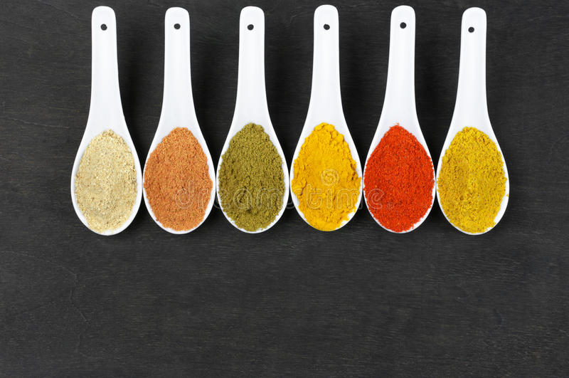 Assorted powder spices. In white spoons on black wood. Top view point stock image