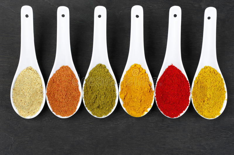 Assorted powder spices. In white spoons on black wood. Top view point royalty free stock image
