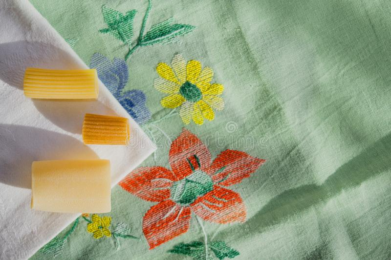 Assorted raw pasta on a colored table-cloth. Assorted raw pasta in sigle file on a colored table-cloth royalty free stock images