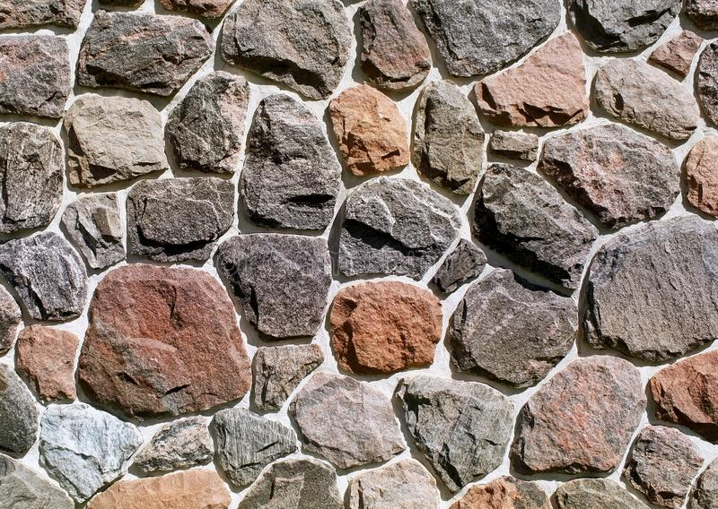 Assorted rocks of different sizes and colors embedded in concrete on an exterior rock wall royalty free stock images