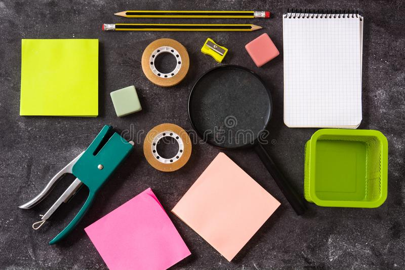 Assorted of school supplies on black slate. Back to school concept. royalty free stock images