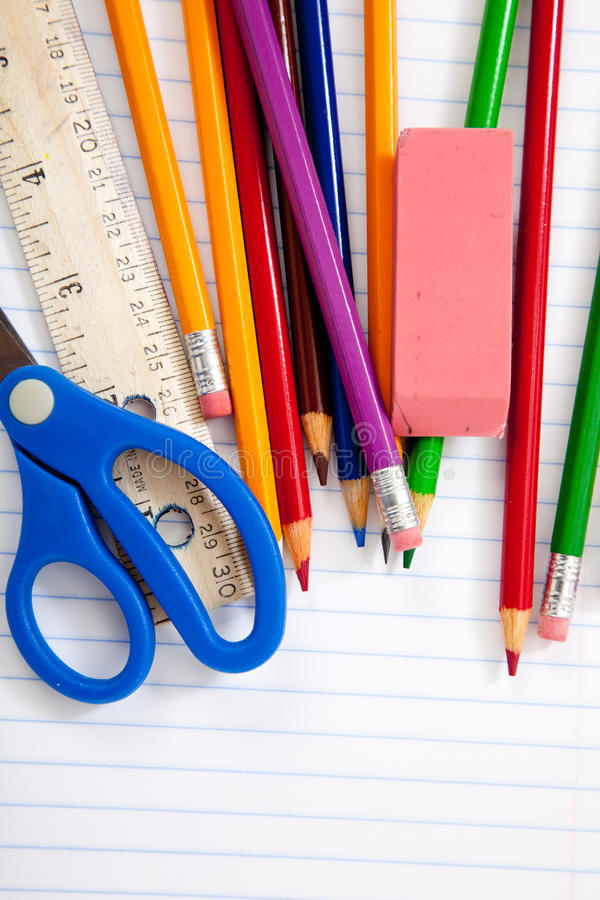 Assorted School Supplies on a lined notebook. A group of assorted school supplies on a lined spiral notebook with copy space royalty free stock images