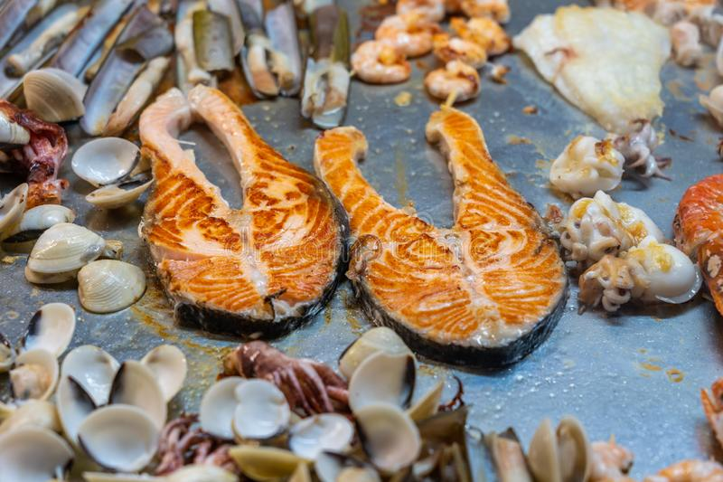 Assorted seafoods on big frying table in restaurant`s kitchen stock photo
