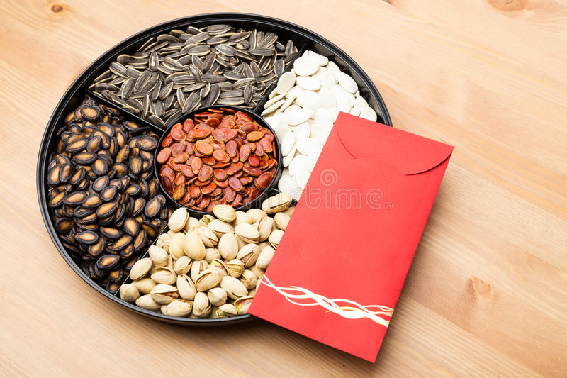 Assorted Snack box and red pocket for Lunar new year. Assorted Snack box and red pocket over the wooden background for Lunar new year royalty free stock photos