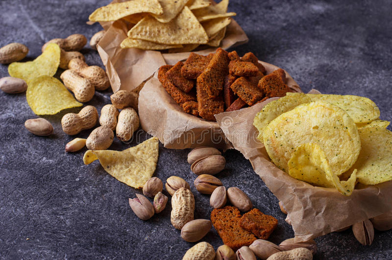 Assorted of snack. Chips, pistachios, nachos and peanuts. Selective focus stock image