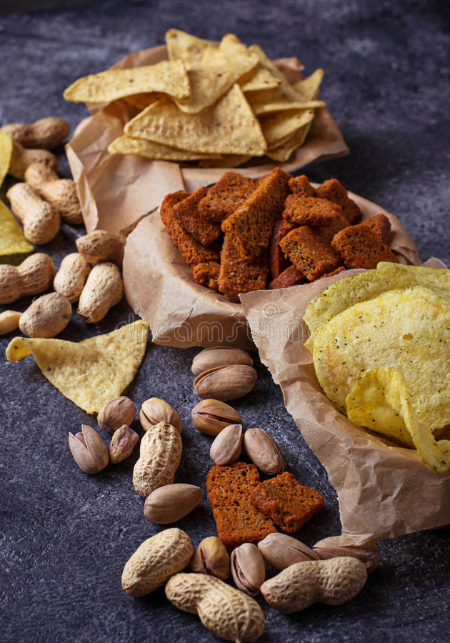 Assorted of snack. Chips, pistachios, nachos and peanuts. Selective focus royalty free stock photography