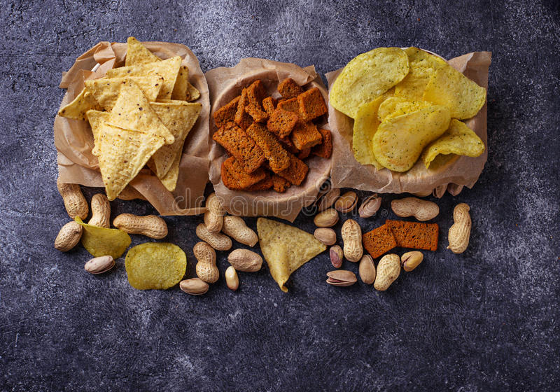 Assorted of snack. Chips, pistachios, nachos and peanuts. Selective focus stock photo