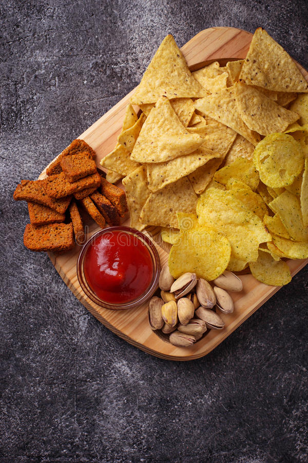 Assorted of snack. Chips, pistachios, nachos and peanuts. Selective focus royalty free stock photos