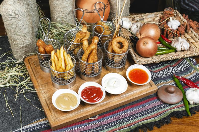 Assorted snacks on the company in the oriental style - onion rings, sausages on skewers royalty free stock photos