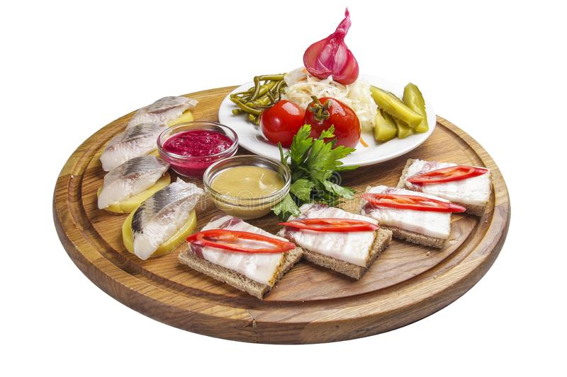 Assorted snacks for vodka. Salo with mustard and horseradish. Homemade pickled vegetables. Herring with potatoes. On the rustic stock images