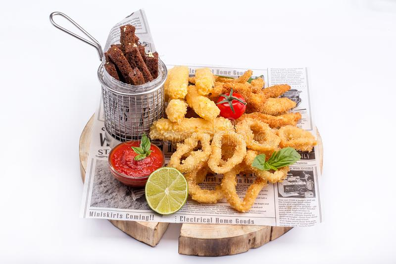 Assorted snacks on white background side view. Calamari in batter, garlic toast, ribs and chicken fillet in batter. stock images