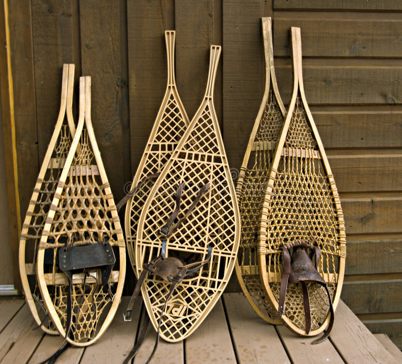 Assorted snowshoes. Traditional Canadian snowshoes, focus on the left pair royalty free stock images