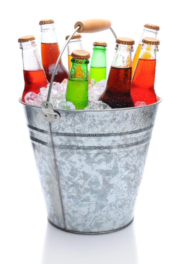 Assorted Soda Bottles in Ice Bucket. Assorted soda bottles in a metal bucket full of ice. Vertical format over white with reflection royalty free stock photos