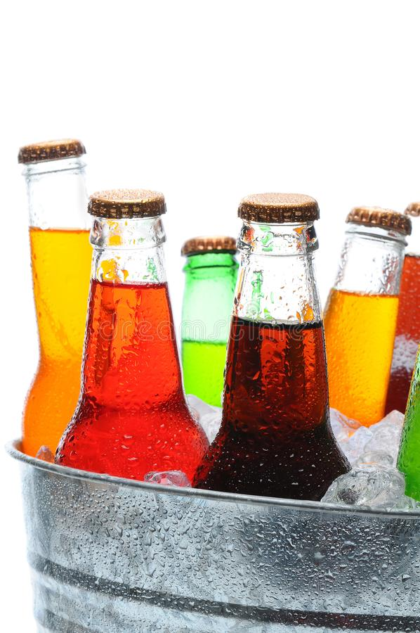 Assorted Soda Bottles in Bucket. Assorted soda bottles in a metal bucket filled with ice. Closeup on white with bottles covered in condensation stock image