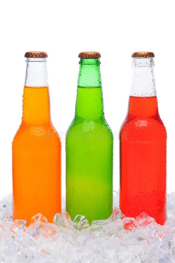 Assorted Soda Bottles Standing in Ice. Closeup of three different soda bottles covered in condensation standing in a bed of ice. Vertical format over white royalty free stock photography