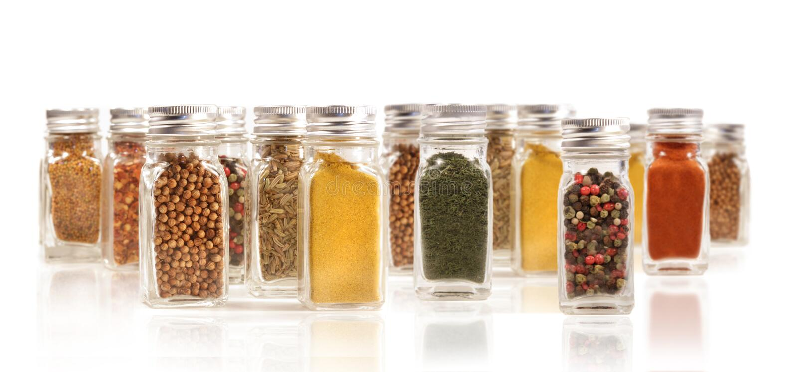 Assorted spice bottles isolated on white royalty free stock photo