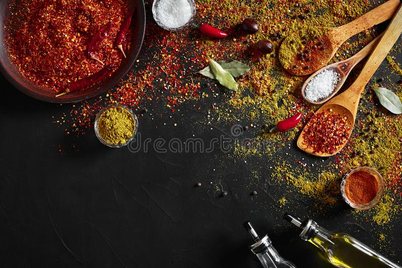 Assorted spices on dark black background. Seasonings for food. Curry, paprika, pepper, cardamom, turmeric. Top view. royalty free stock images