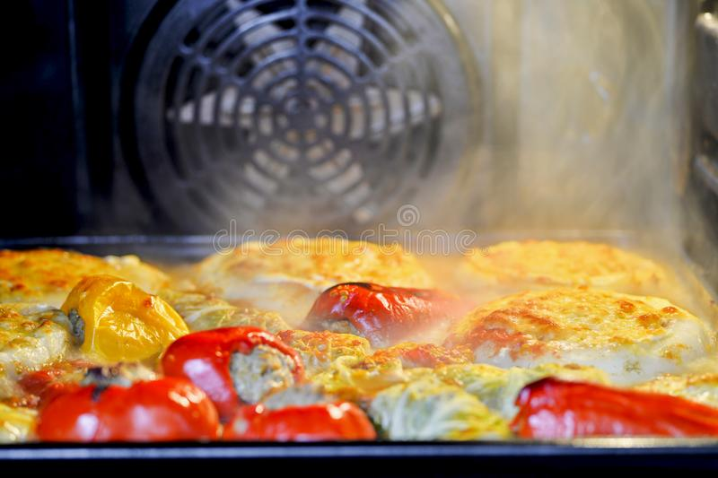 Assorted stuffed peppers, stuffed cabbage and zucchini on a baking sheet in the oven royalty free stock photography