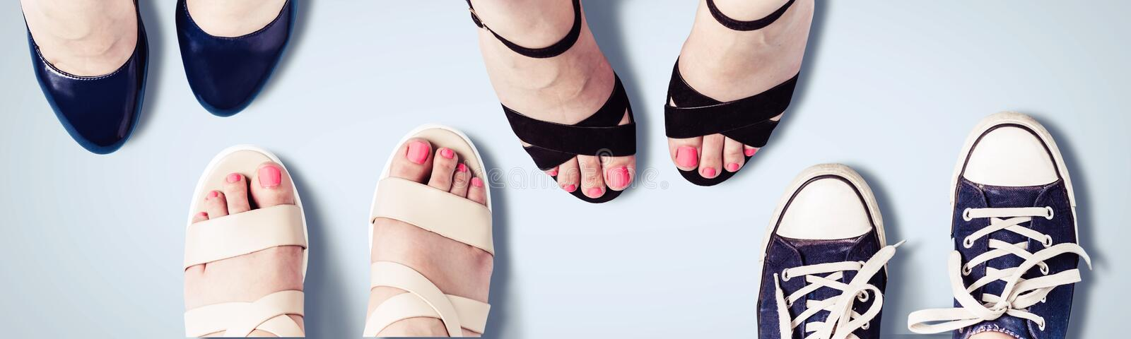 Assorted summer women`s shoes. Female feet in sandals, sneakers, shoes. stock photos