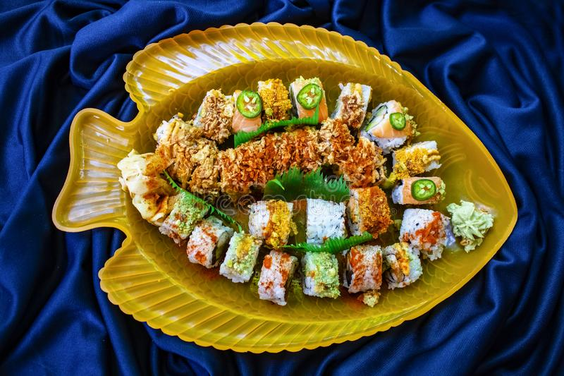 Assorted sushi rolls arranged in a yellow fish platter with blue scrunched fabric background stock photo