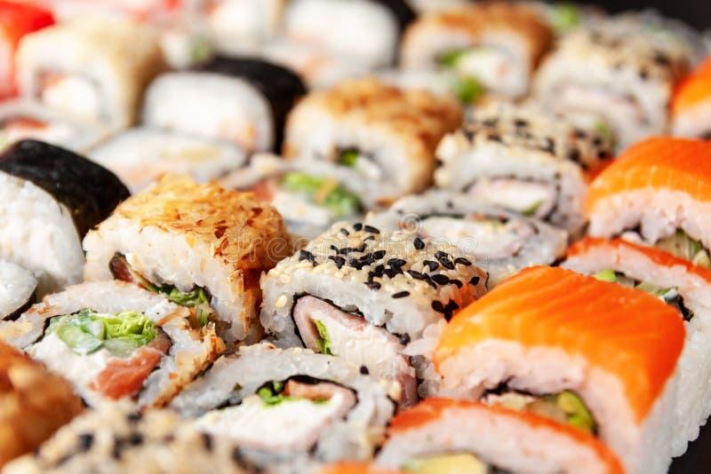 Assorted sushi rolls on black background stock photography