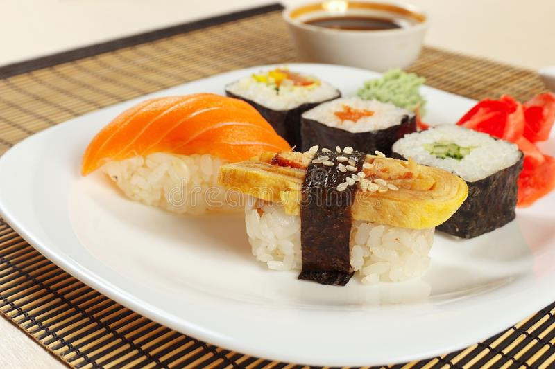 Assorted sushi and rolls and soy sauce on bamboo mat close up. royalty free stock image
