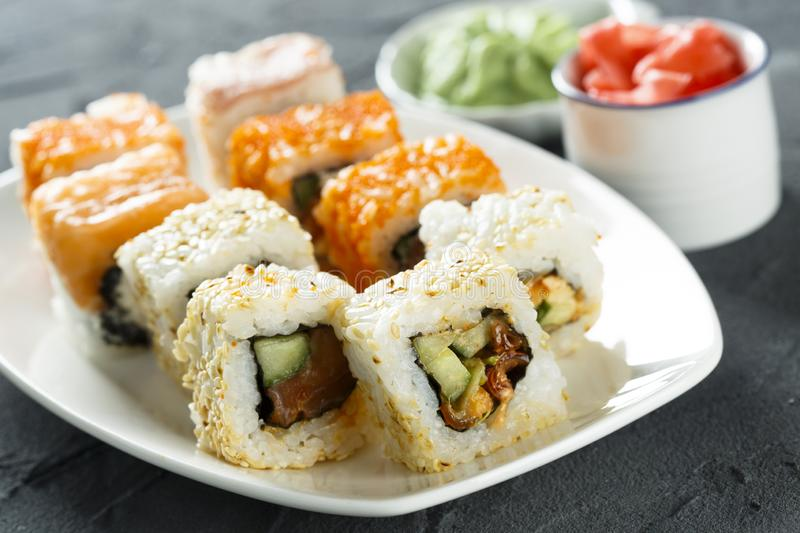 Assorted sushi and rolls on a white plate stock photo