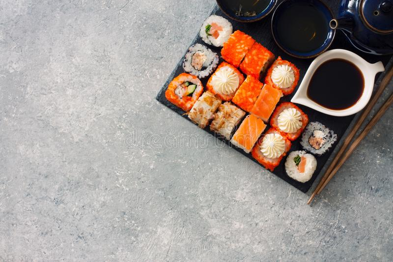 Assorted sushi and tea set served on a black stone slate stock photos