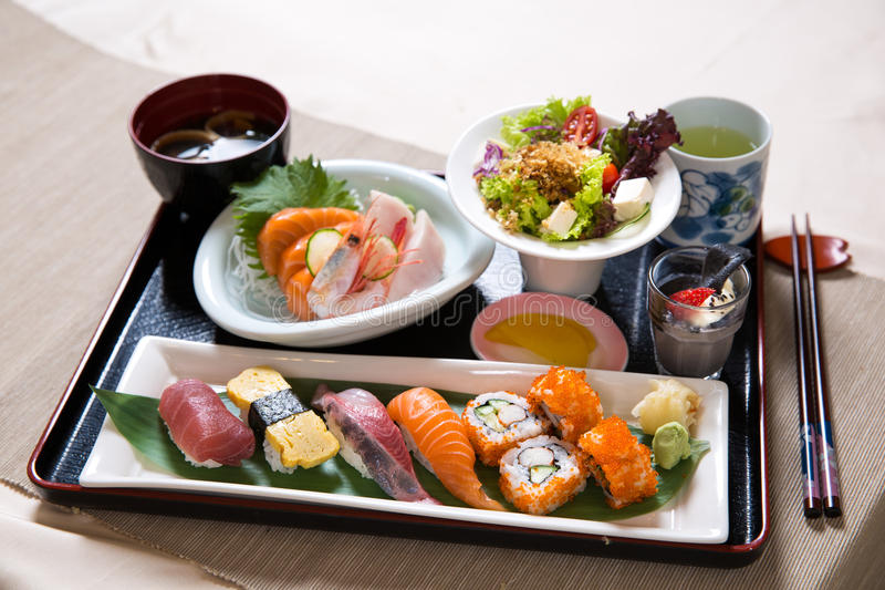 Assorted Sushi Tray Set. Assorted sushi and sashimi with salad on a tray royalty free stock image
