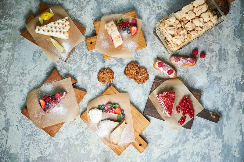 Assorted sweet desserts. Top view. Gray textured background. Beautiful serving dishes. Dessert. Food chain royalty free stock photos