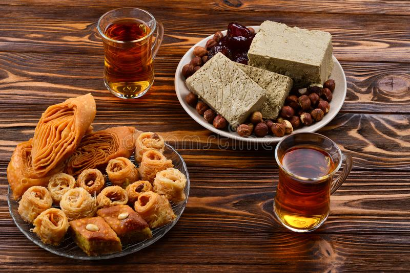 Assorted traditional eastern desserts with tea on wooden background. stock image