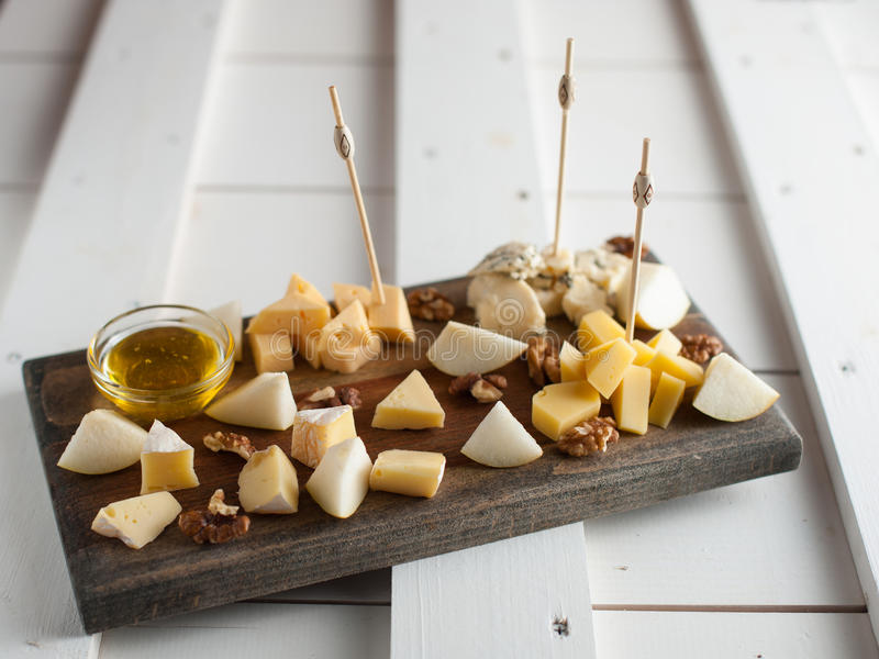 Assorted variety of cheese with honey and nuts. Placed on a dark wooden board. Assortment of different types of cheese with natural honey and walnuts. Placed on royalty free stock photography