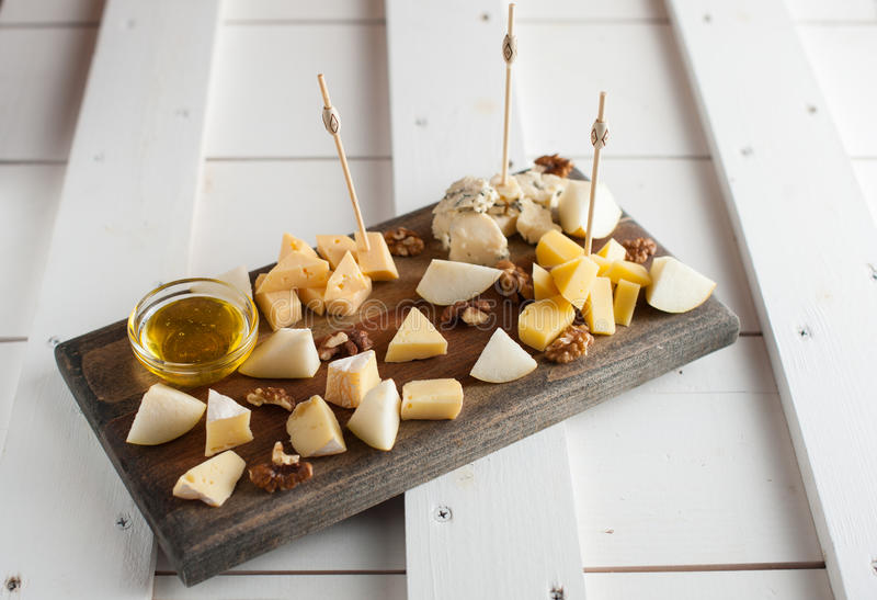 Assorted variety of cheese with honey and nuts. Placed on a dark wooden board. Assortment of different types of cheese with natural honey and walnuts. Placed on stock photo