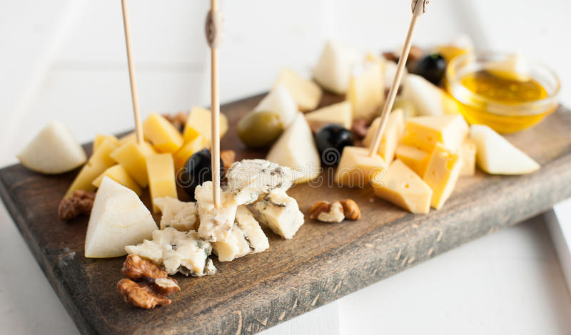 Assorted variety of cheese with honey and nuts. Placed on a dark wooden board. Assortment of different types of cheese with natural honey and walnuts. Placed on stock image