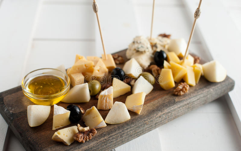 Assorted variety of cheese with honey and nuts. Placed on a dark wooden board. Assortment of different types of cheese with natural honey and walnuts. Placed on stock photography