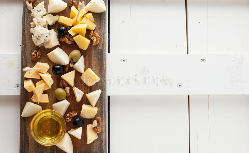 Assorted variety of cheese with honey and nuts. Placed on a dark wooden board. Assortment of different types of cheese with natural honey and walnuts. Placed on royalty free stock photos
