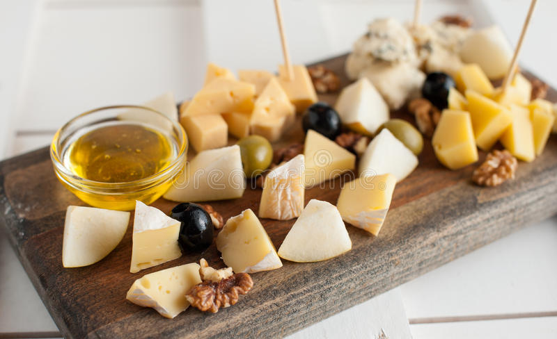 Assorted variety of cheese with honey and nuts. Placed on a dark wooden board. Assortment of different types of cheese with natural honey and walnuts. Placed on stock photos